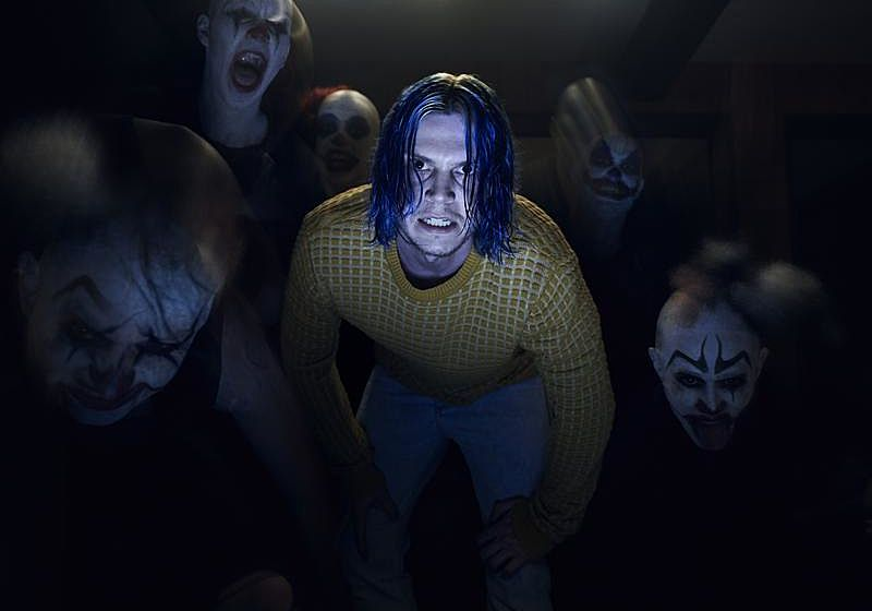 Kai Anderson in a yellow sweater surrounded by creepy clowns