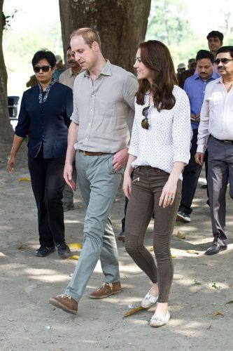 Kate Middleton walking with Price Harry outdoors.
