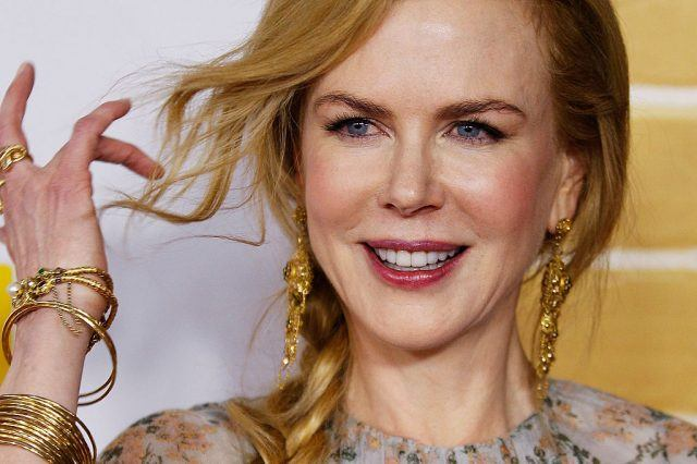 Nicole Kidman wearing elaborate jewelry and adjusting her hair while posing for photos at a red carpet.