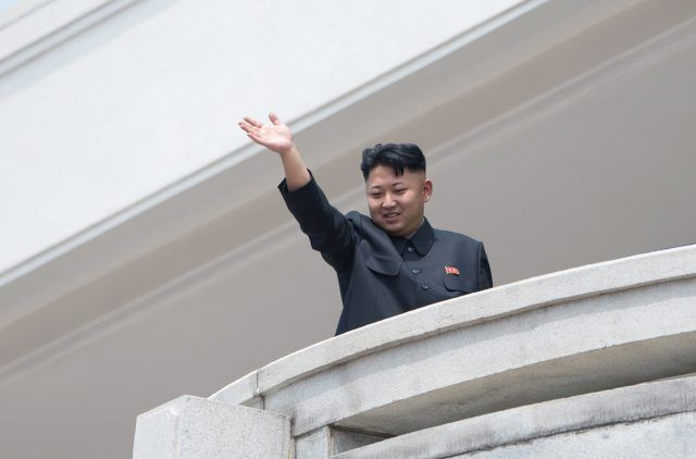 Kim Jong Un waving from a balcony.