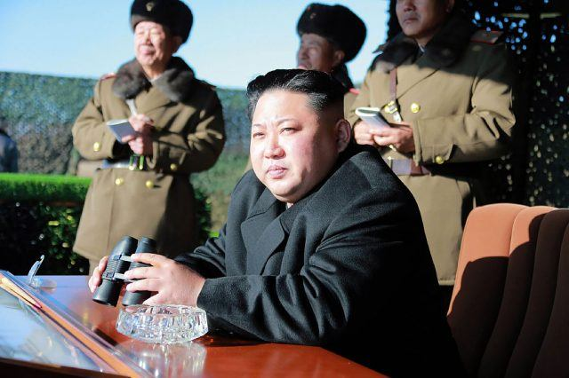 Kim Jong-Un sitting at a desk while holding binoculars.