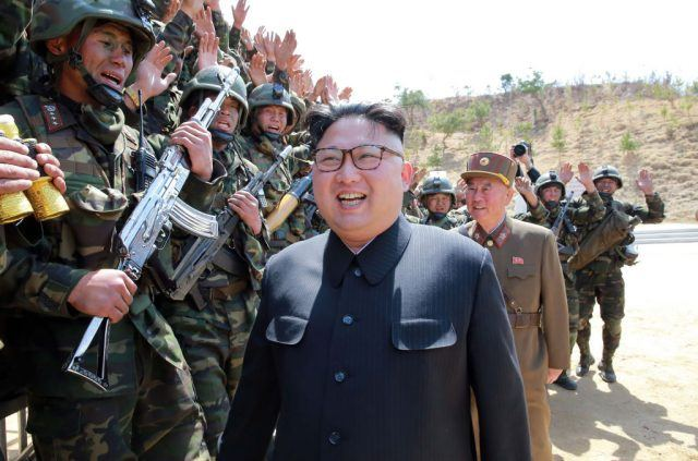 Kim Jong Un walking past a military group.