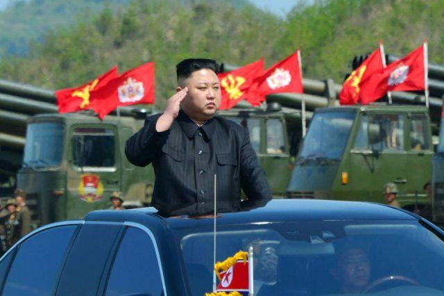 Kim Jong Un waves from the top of a vehicle.