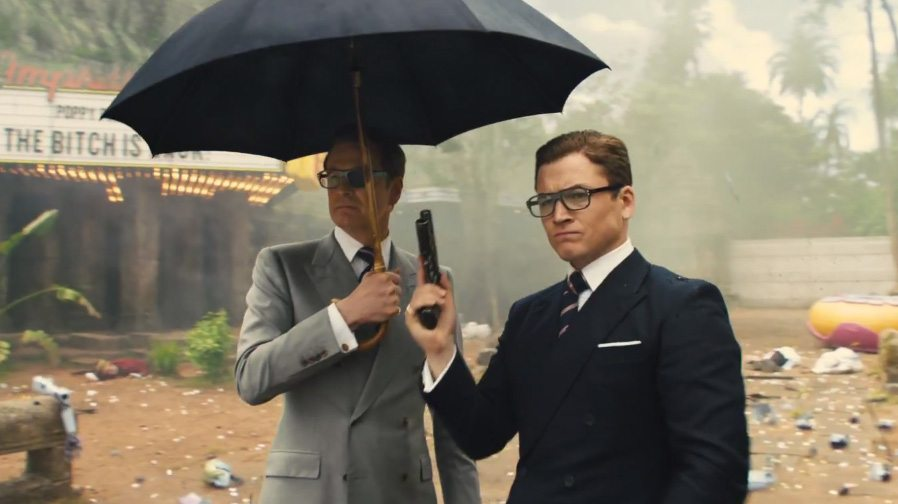 Colin Firth and Taron Egerton stand next to each other while holding a gun and umbrella