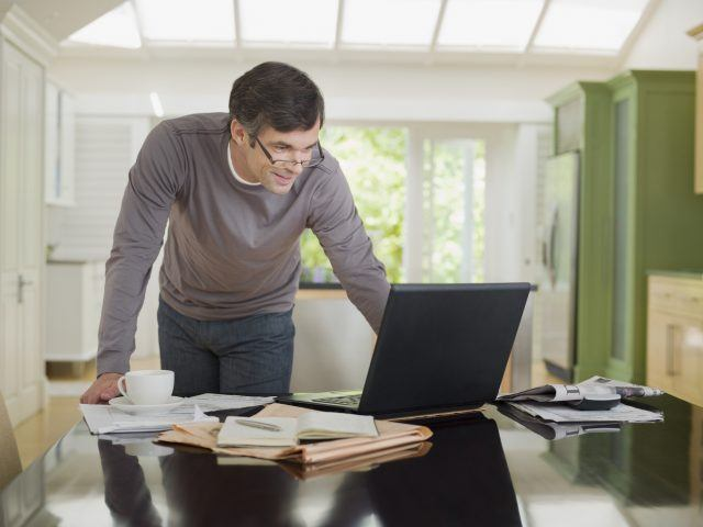 Man at kitchen desk in front of laptop.