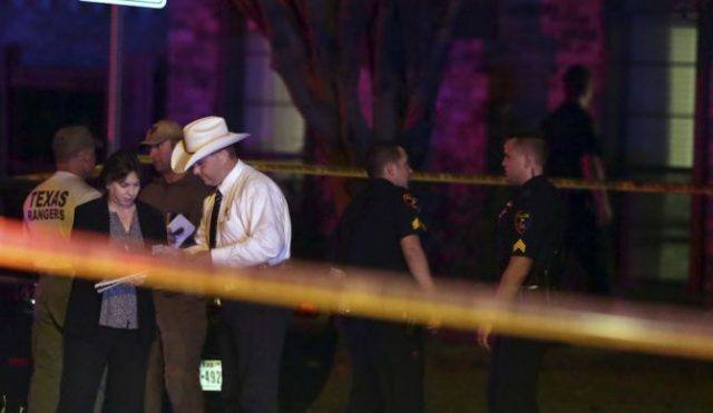 Investigators comb the area outside a home in Plano Texas, where eight people were killed by gunfire on Sunday night.