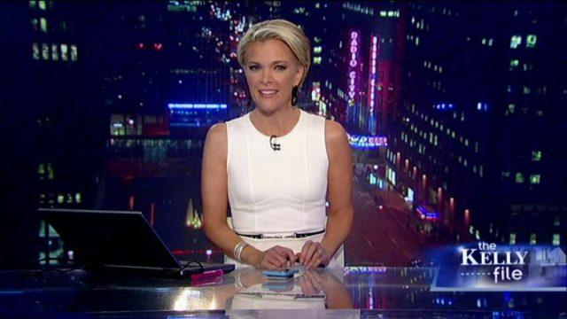 Megyn Kelly sitting at a news desk with a phone and laptop in front of her.