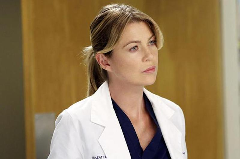 Meredith Grey stands in a white doctor's coat and looks ahead