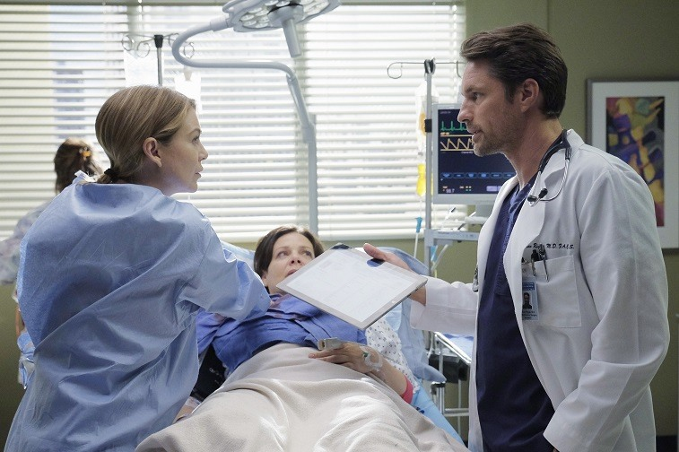 Meredith and Riggs in a patient's room working together on Grey's Anatomy