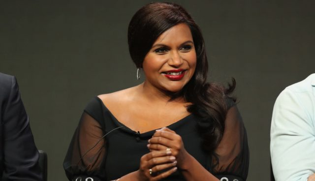 Mindy Kaling holding her hands in front of herself while sitting on stage during a panel in a black dress.