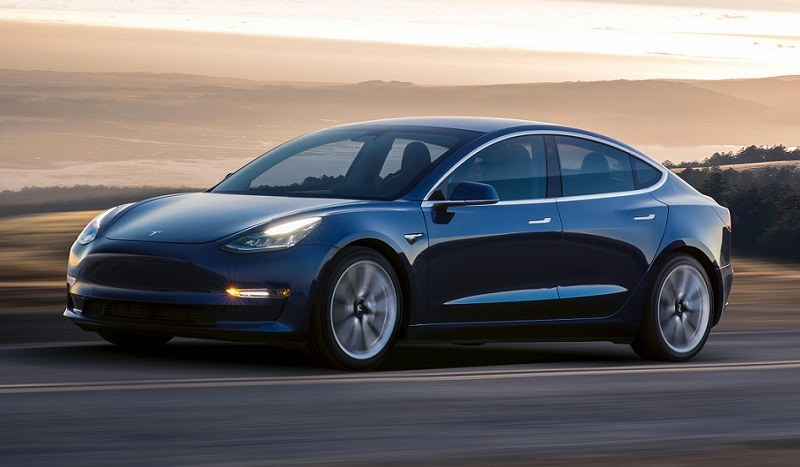 Profile view of Tesla Model 3 in motion on California road