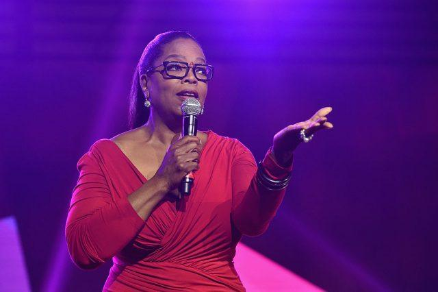 Oprah Winfrey holding a microphone in one hand while raising her other hand.