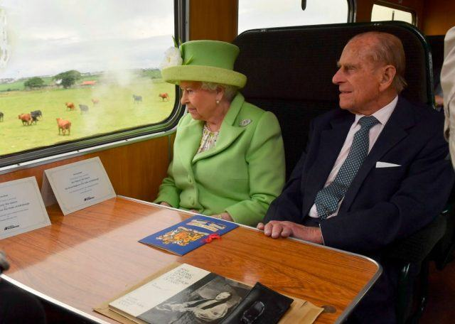 Queen Elizabeth and Prince Phillip on a train.