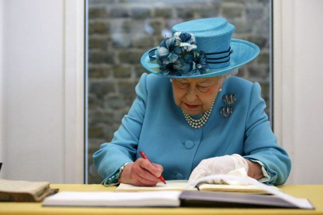 Queen Elizabeth signing a document in her book.