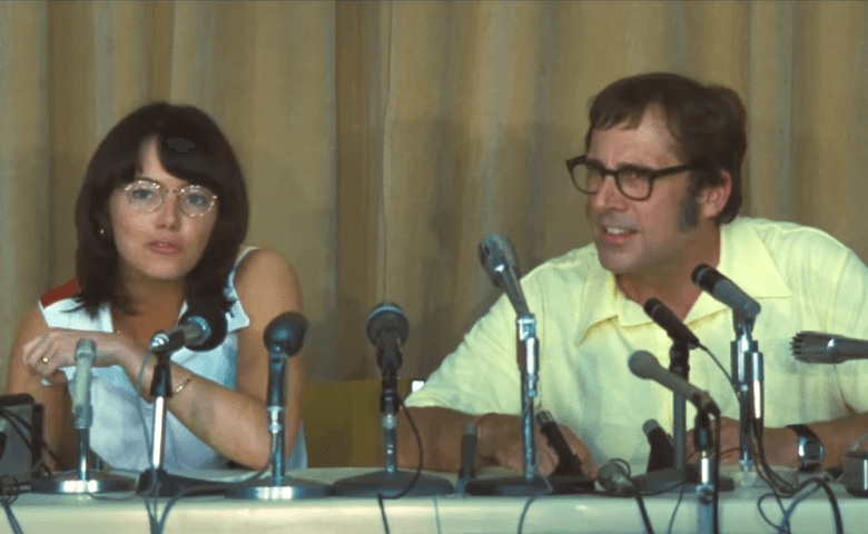 Emma Stone and Steve Carell sit next to each other in front of microphones in Battle of the Sexes