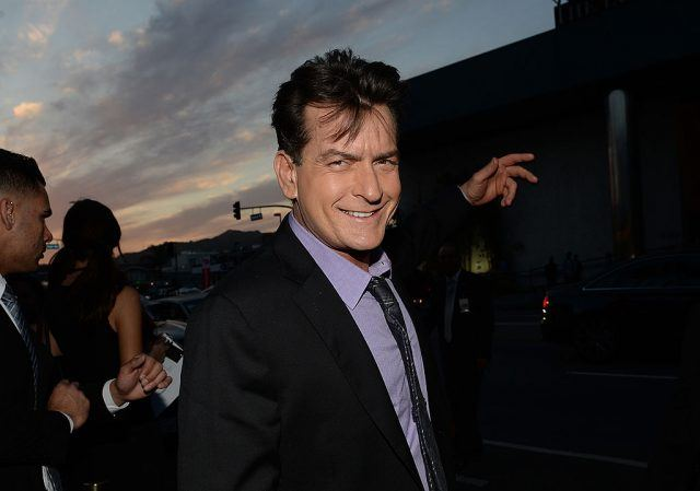 Charlie Sheen at the Scary Movie V premiere in a purple dress shirt and dark suit.