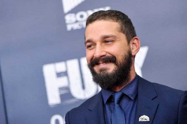 Shia LaBeouf smiling while wearing a blue suit on a red carpet.