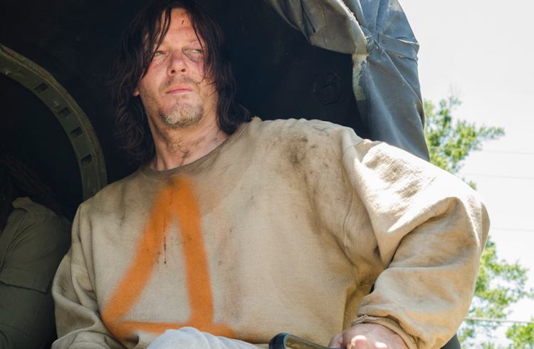 Daryl sits at the back of a truck wearing a garment with the number 4 on it