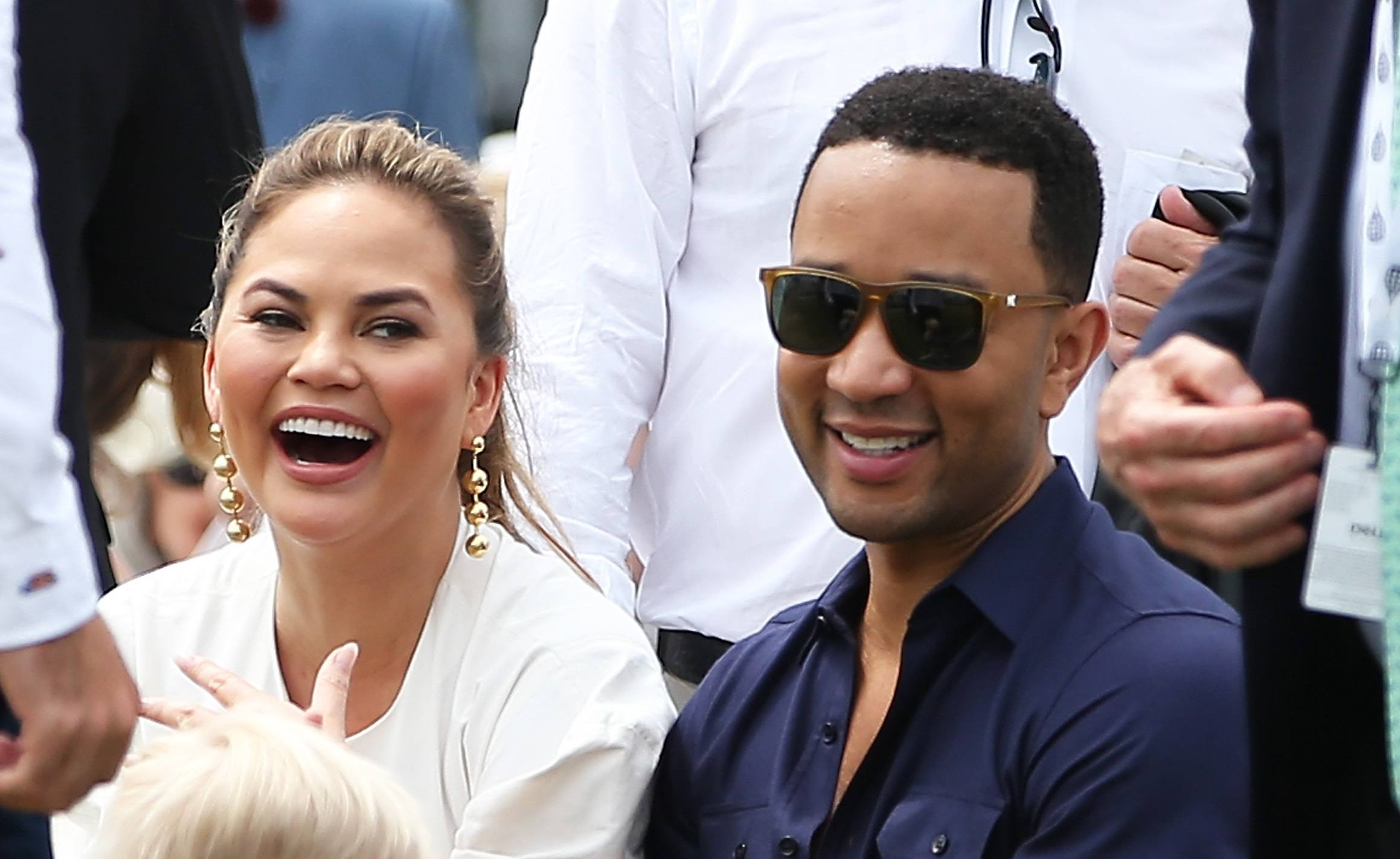 John Legend and Chrissy Teigen look on during the Tennis Hall of Fame induction ceremonies at the International Tennis Hall of Fame on July 22, 2017 in Newport, Rhode Island.