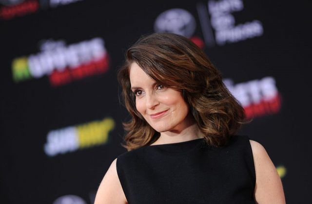 Tina Fey standing in a black dress smiling and staring straight ahead.