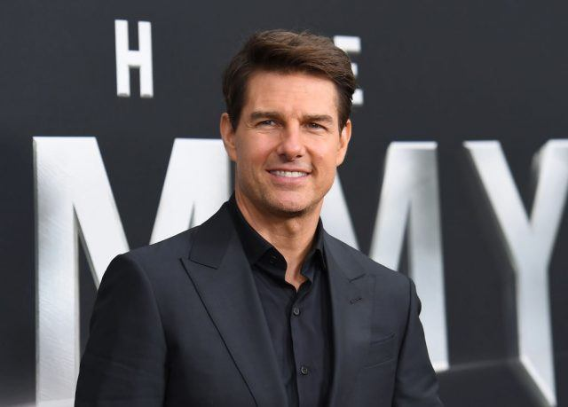 Tom Cruise smiling in a black suit at the premiere of 'The Mummy.'