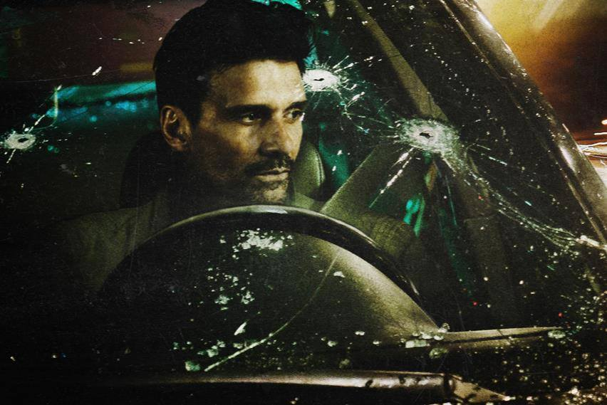 A man sits behind the wheel of a car with a bullet-ridden windshield