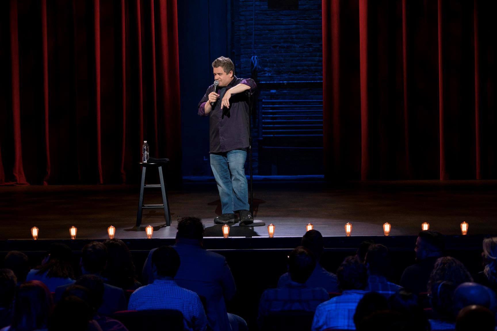 Patton Oswalt stands on stage holding a microphone
