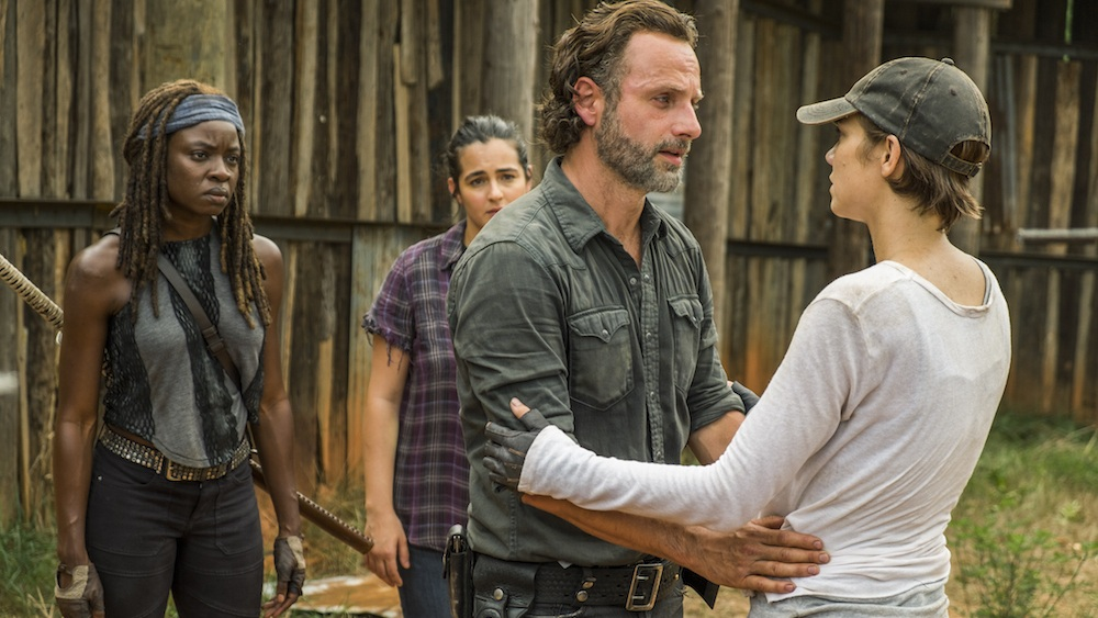 Rick faces Maggie and puts his hand on her waist