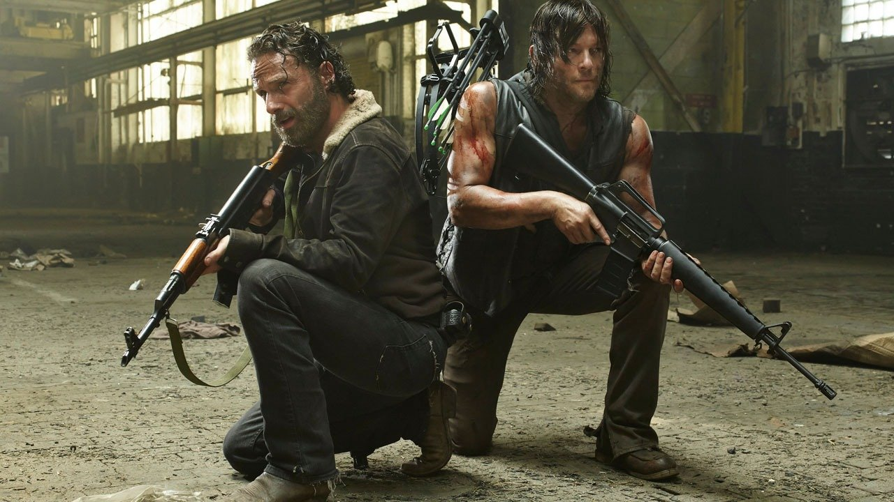 Rick and Daryl crouch next to each other while holding rifles