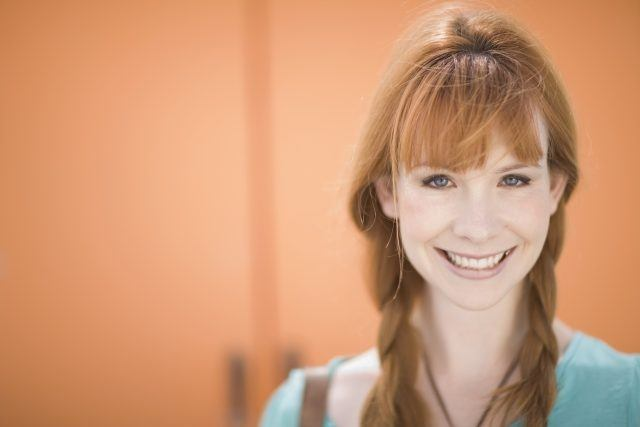 Woman with red hair smiling in front of an orange wall.