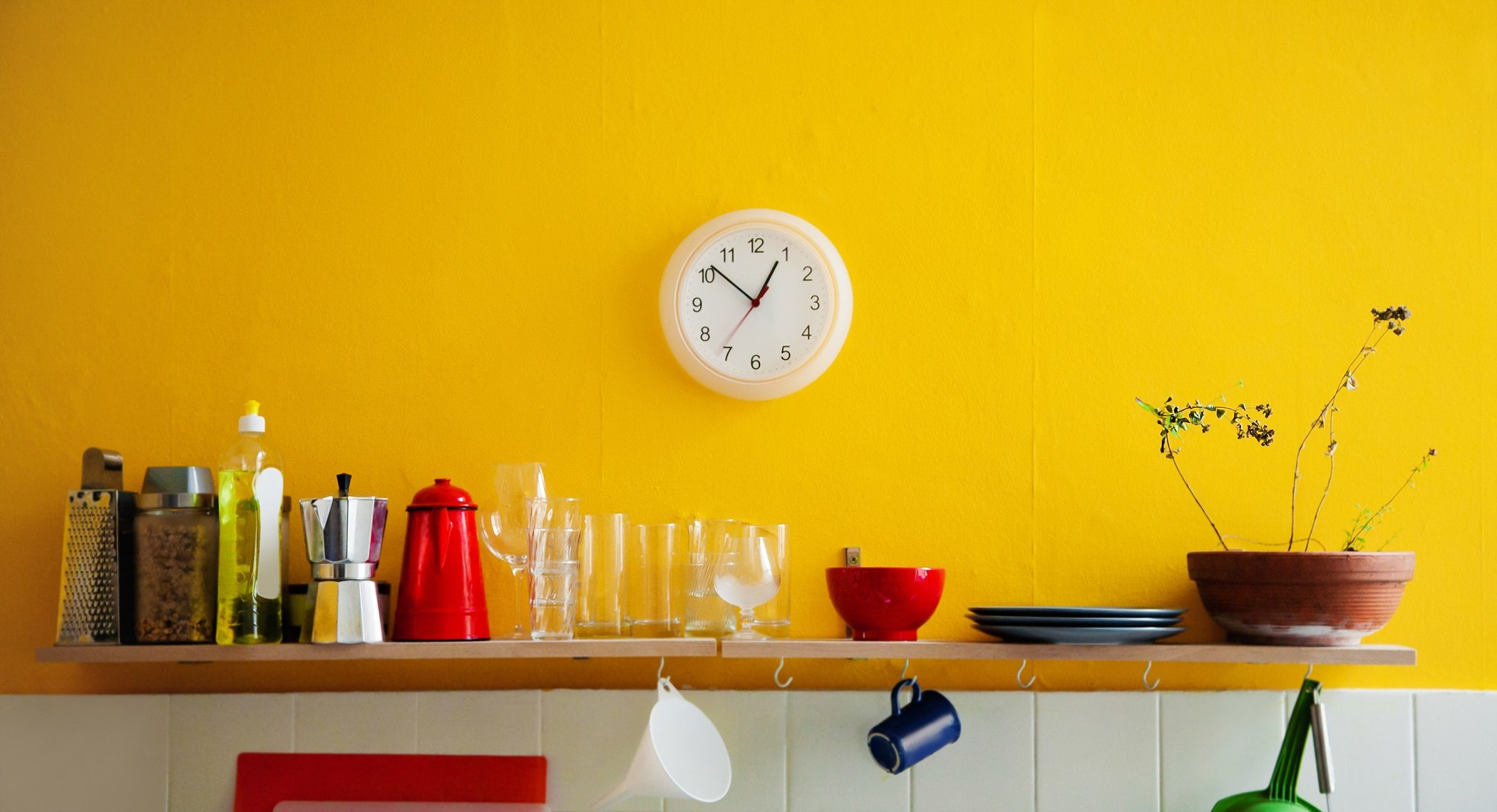 Yellow wall in kitchen with shelf and clock