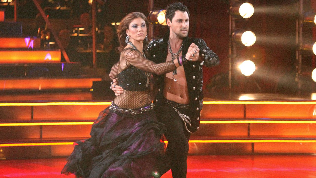 Maksim Chmerkovskiy and Hope Solo hold hands while dancing in black sequin outfits