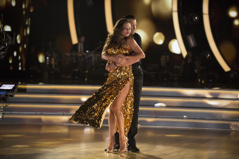 Vanessa Lachey dances in a gold dress with her partner on DWTS