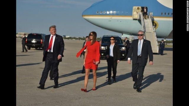 Donald and Melania Trump walk away from Air Force One on the tarmac surrounded by 4 Secret Service agents