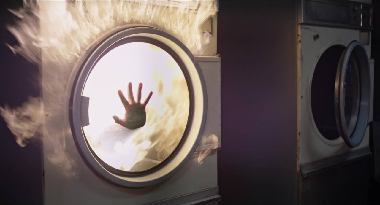 A hand is seen pressed up against a washing machine in the New Mutants trailer