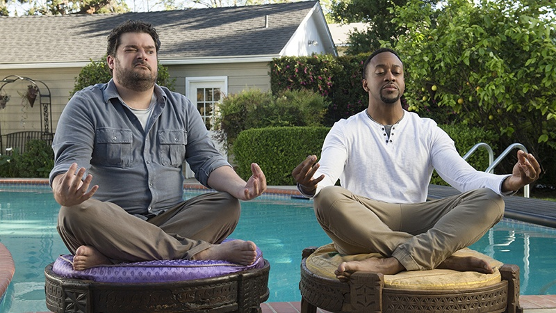 Two men sit next to each other in meditation poses