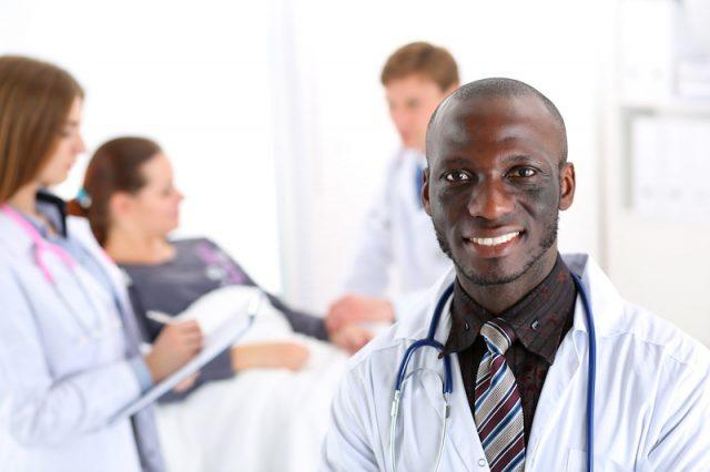 A doctor smiles while sitting in front of a patient.