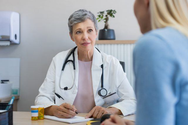 A doctor writing down notes while speaking to a patient.