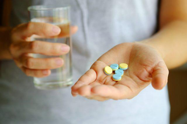 A person holding medication in one hand and a glass of water in the other.