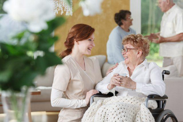 Nurse and patient talking in nursing home.