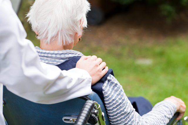 A nurse pushes a patient in a wheelchair outdoors.