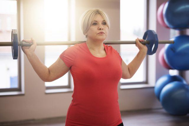 A woman working out in a gym with a weight bar.