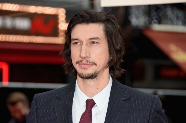 Adam Driver posing for photos on a red carpet in a dark suit and red tie.