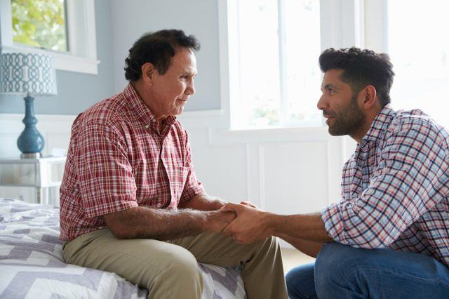 A man holding hands with an elderly man in a nursing home