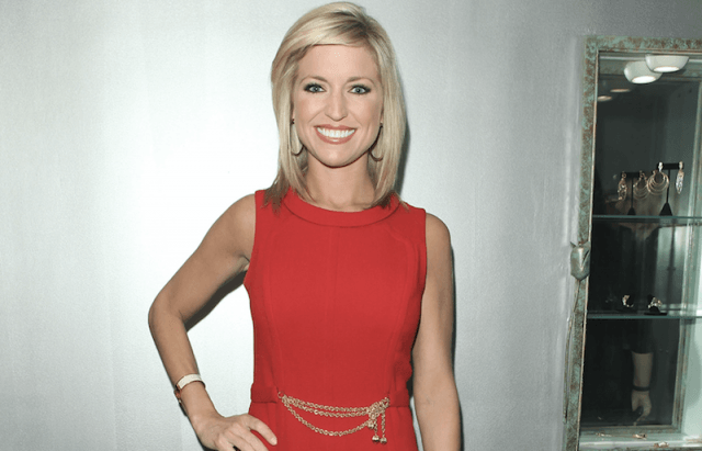 Ainsley Earhardt standing in a red dress with one hand on her hip.