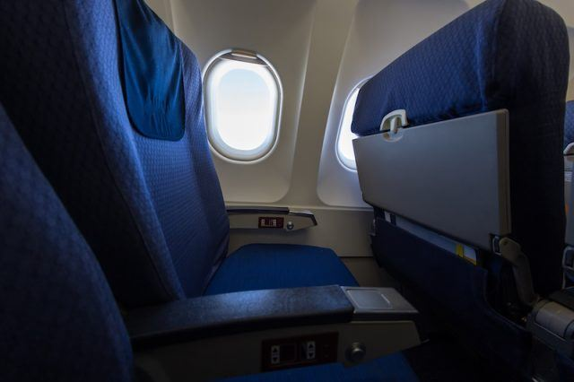 Empty blue airplane seats on a plane.