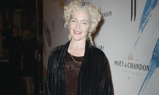 Amy Irving smiling in a suede black jacket and brown top.