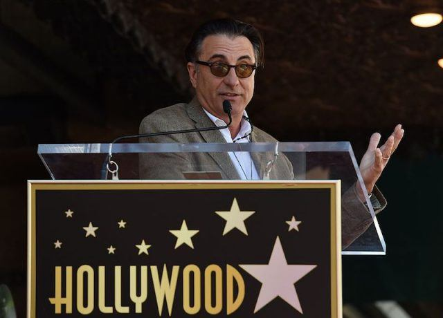 Andy Garcia speaking to the public in front of a podium.