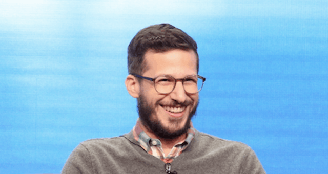 Andy Samberg laughs behind a blue screen.