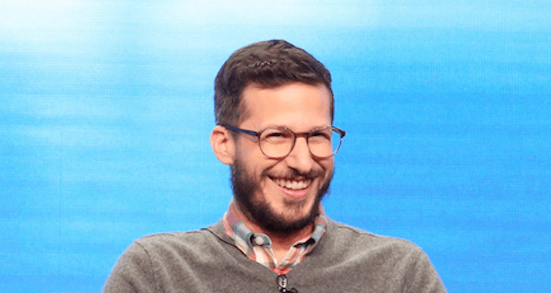 Andy Samberg laughing in front of a blue screen